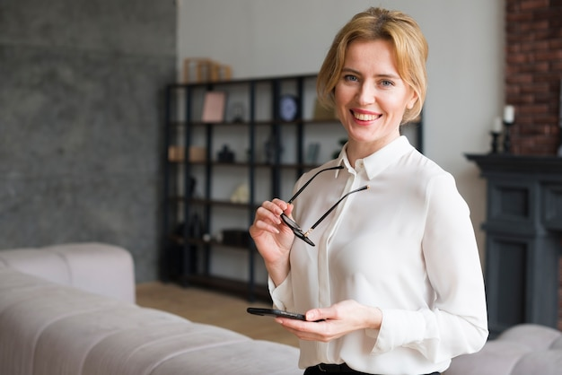 Blond business woman using smartphone