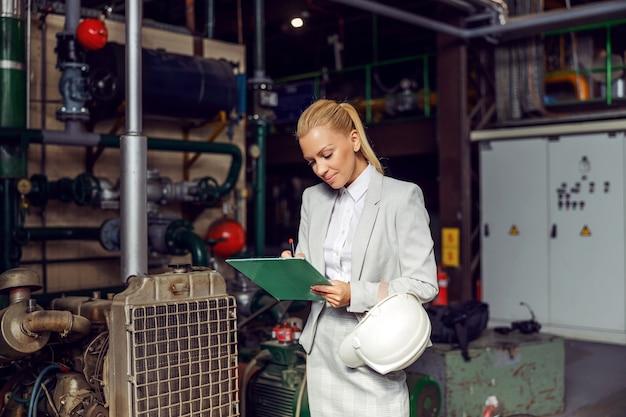 공장 난방, 클립 보드를 누른 기계 검사에 서 금발 사업가.