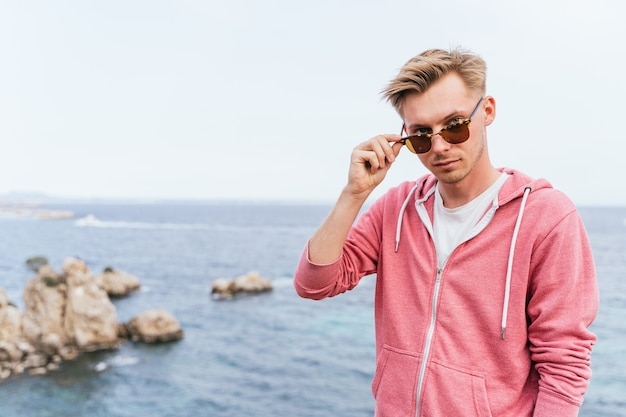 Blond caucasian man looking straight ahead while removing his sunglasses from his face. palma de mallorca, spain (perfect for copyspace)