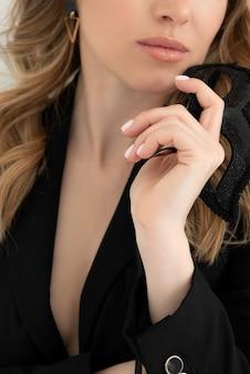 금발의 백인 여자는 그녀의 손에 검은 카니발 마스크를 보유