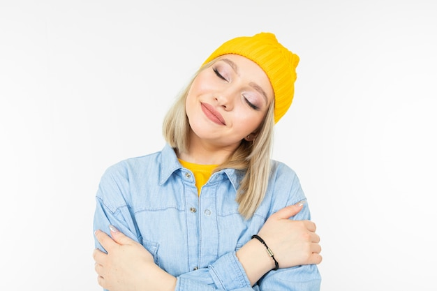 Blond charming young woman in casual look with jeans shirt hugs herself on a white background