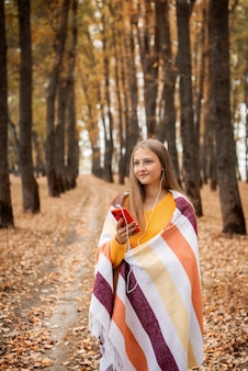 가을 공원의 공원 보도에 서서 헤드폰으로 음악을 듣고 있는 금발의 쾌활한 소녀. 땅에 노란 단풍, 웃는 사람.