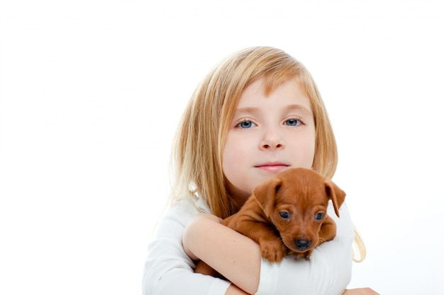 Blond children girl with dog puppy mini pinscher