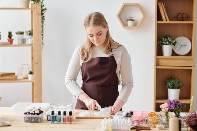 Блондинка мастерица в коричневом фартуке готовит твердую мыльную массу для дальнейшей обработки во время работы в студии