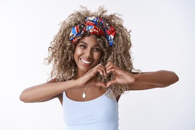 スタイリッシュなヘッドバンド、ピアスとトップの金髪の巻き毛の女の子、ハートのサインが愛と幸福を表現し、嬉しそうに笑って、ロマンチックな気持ちを告白し、白い壁を表示します