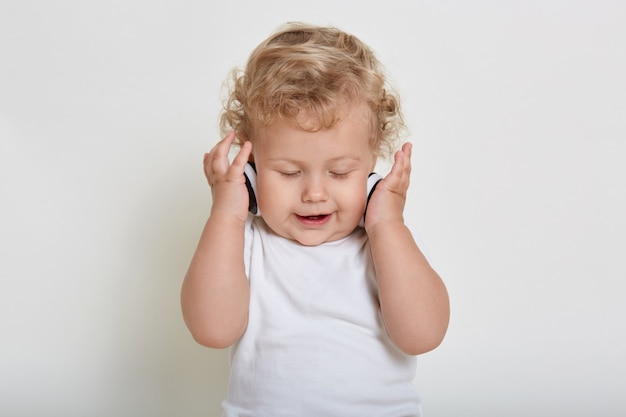 Blond curly haired baby with headphones on white space, child enjoying music with closed eyes