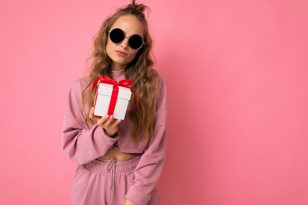 Blond curly woman isolated over pink background wall wearing