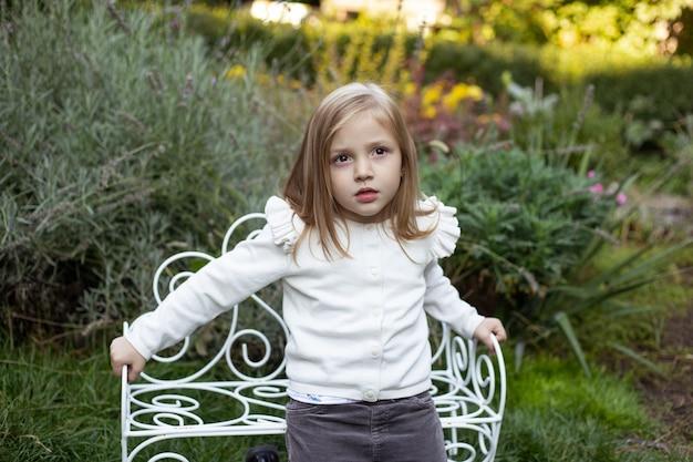 Blond cute girl near the bush on bench in summer