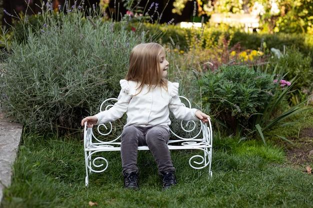 Blond cute girl in summer near the bush on bench