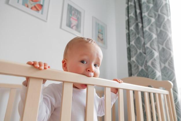 Блондинка милый маленький ребенок кусает деревянное изголовье кровати