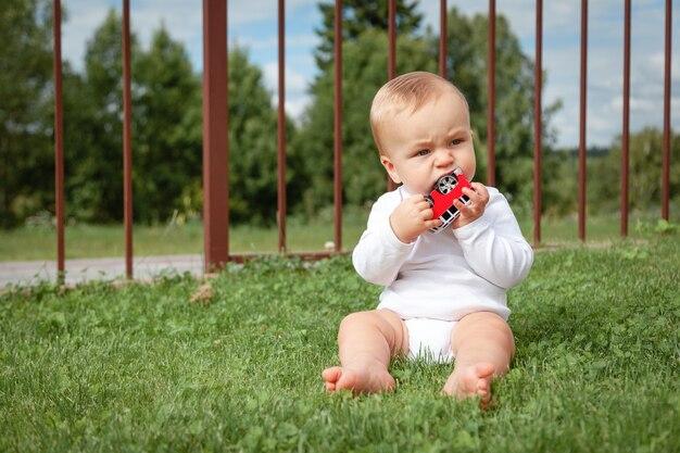 푸른 잔디에 앉아서 자동차 장난감을 가지고 노는 흰색 bodysuit에서 금발의 귀여운 작은 파란 눈 아기.