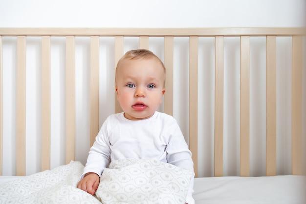 Блондинка милый маленький голубоглазый ребенок в белом боди сидит в деревянной кровати