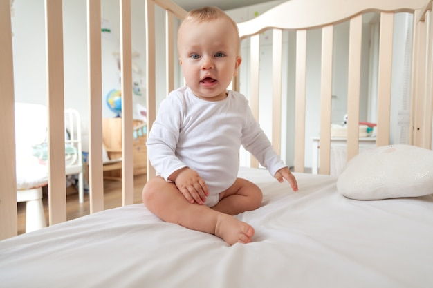 Blond cute little blue-eyed baby in white bodysuit sitting in wooden bed