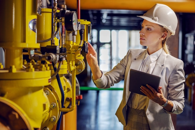 Blond dedicated successful businesswoman in formal wear checking on machinery and holding tablet while standing in power plant.