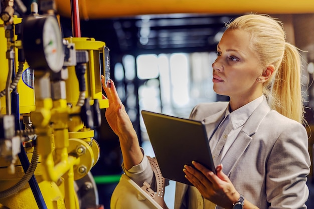 Blond dedicated successful businesswoman in formal wear checking on machinery and holding tablet while standing in power plant