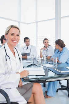 Blond doctor sitting next to her medical team in a bright office