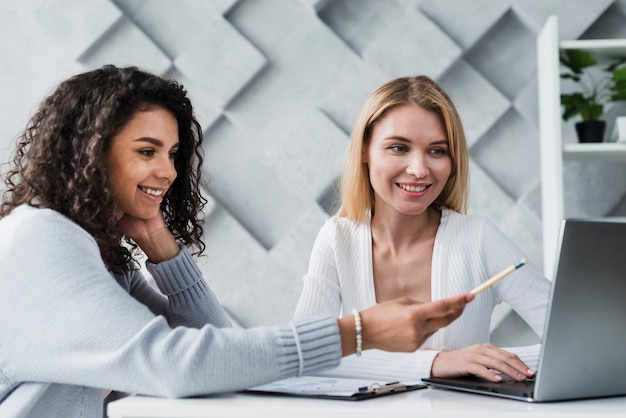 Blond and ethnic coworkers working with laptop