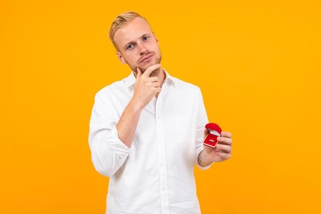 Белокурый европейский мужчина делает предложение, держа кольцо в коробке на желтом фоне.