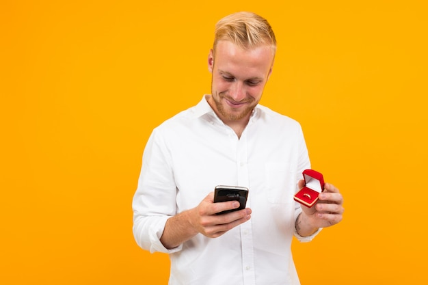 Белокурый европейский человек делает предложение держа кольцо в коробке и телефон на желтом цвете.
