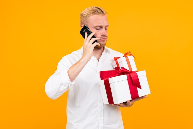 Blond european young man in a white shirt holds a gift box b is talking on the phone on a yellow background.