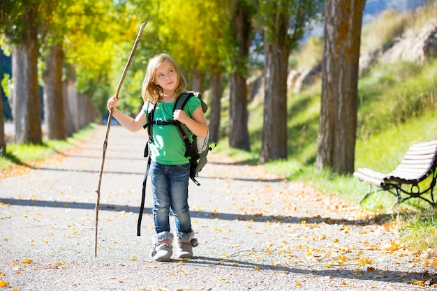 Blond explorer kid girl walking with backpack in autumn trees
