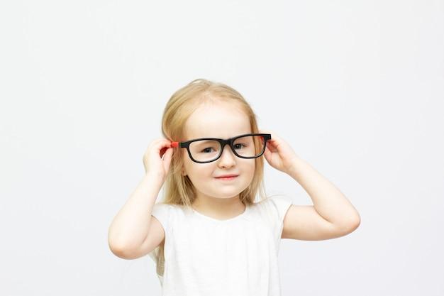 白で隔離赤と黒のメガネの肖像画と金髪のファッションの子供の女の子
