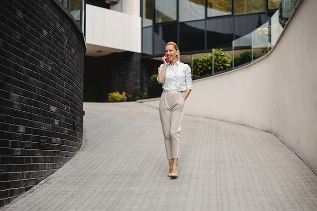 Blond fashionable businesswoman talking on the phone in business center exterior.