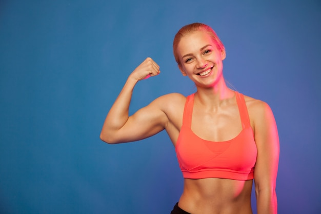Blond female athlete showing biceps on blue background,