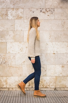 Blond female in casual clothwalking turning aside