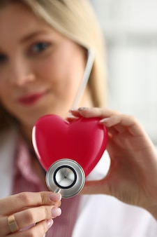 Blond female doctor hold in arms red toy heart closeup