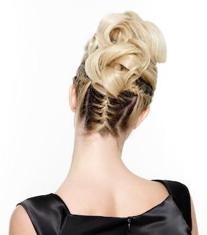 白の創造的な巻き毛の髪型を持つ金髪の女性