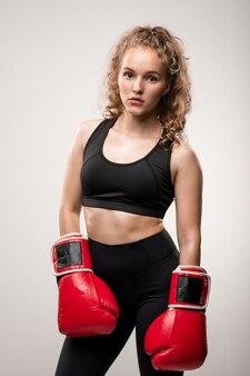 スポーツクラブやジムでのトレーニングの準備ができている黒いトラックスーツと赤いボクシンググローブの金髪の女の子