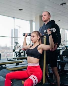 ジムで男性のパートナーインストラクターと一緒にベンチに座っている間彼女の頭の上にダンベルベンチを押してスポーツウェアでブロンドフィットの女性