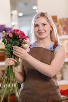 꽃 가게의 작업 공간에서 앞치마에 금발 꽃집 여자. 선택적 초점입니다.