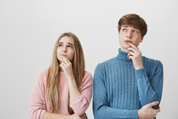 ブロンドの女の子と男は左上隅を見て、考えて、決断する