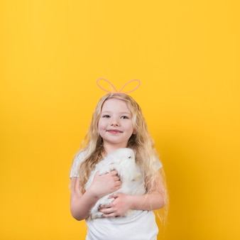Blond girl in bunny ears with cute rabbit
