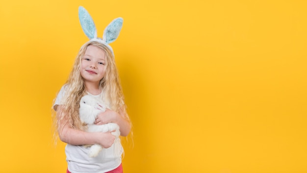 Blond girl in bunny ears with rabbit
