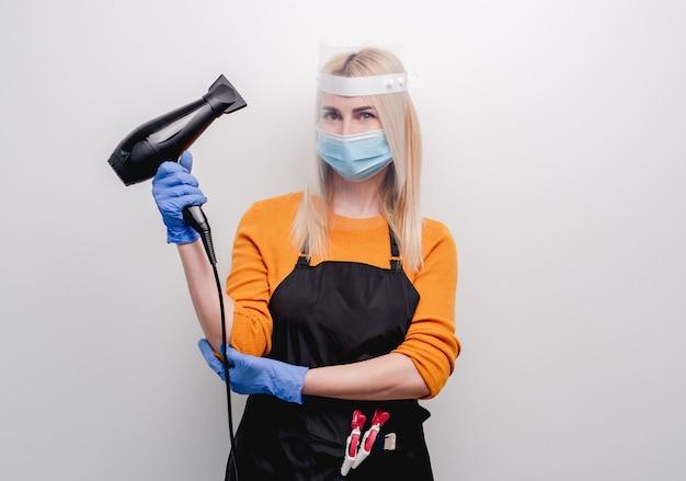 彼女の手でヘアドライヤーを保持している薬のマスクと手袋を身に着けているブロンドの女の子の美容師