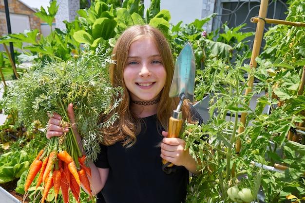 Blond girl harvesting carrots urban orchard