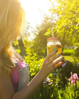 ストローで瓶に新鮮なレモネードを保持しているブロンドの女の子。流行に敏感な夏の飲み物。健康的なビーガンライフスタイル。自然の中で環境にやさしい。ガラスにミントが入ったレモン、オレンジ、ベリー。