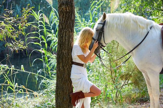 Blond girl hug her horse in magic forest
