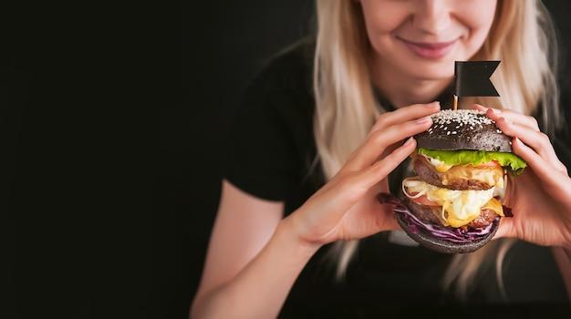 그녀의 손에 큰 검은 햄버거와 검은 티셔츠에 금발 소녀