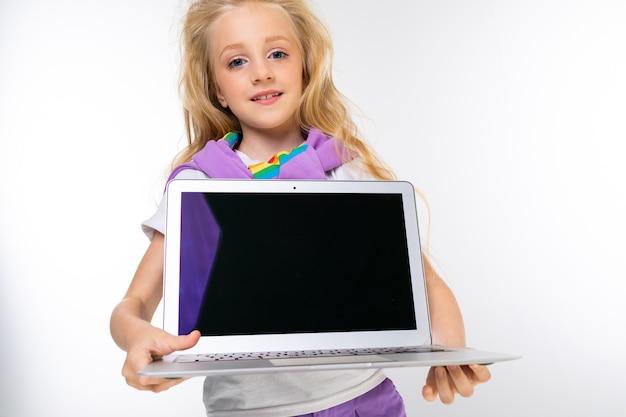 캐주얼 모습에 금발 소녀는 흰색 배경에 모형과 노트북 디스플레이를 보여줍니다.