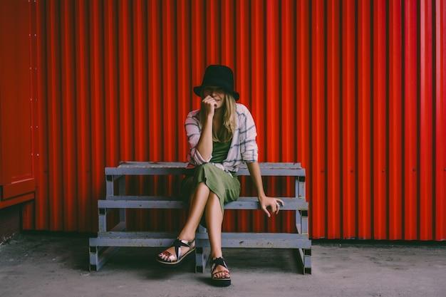 모자에 금발 소녀입니다. 거리 사진. 캐주얼 옷을 입고 아름다운 소녀는 신비하게 웃고있다. 빈티지 스타일