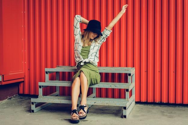 帽子のブロンドの女の子。ストリート写真。カジュアルな服を着た美しい女の子は不思議に笑っています。ビンテージ・スタイル 無料写真