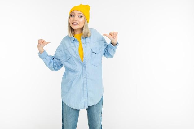 スタイリッシュなデニムシャツと黄色い帽子のブロンドの女の子は、白いスタジオの背景のように表示されます。