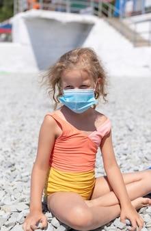 Блондинка в купальнике и защитной маске на галечном пляже