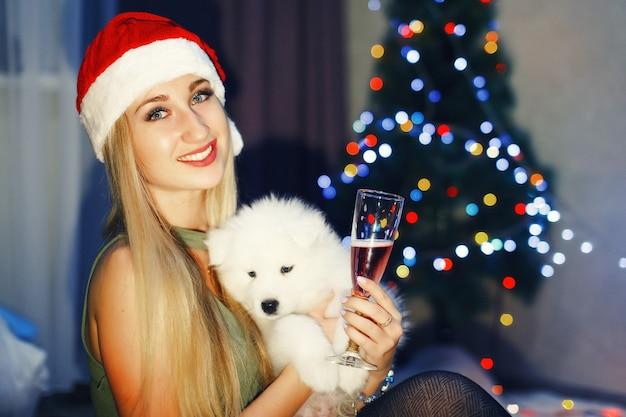 クリスマスの装飾でサモエドハスキー犬と赤いクリスマス帽子のブロンドの女の子