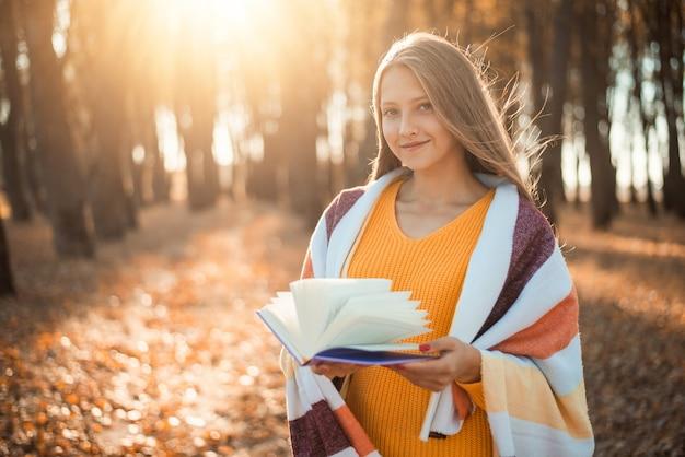 공원에서 손에 시 책을 들고 따뜻한 격자 무늬와 오렌지색 스웨터를 입은 금발 소녀
