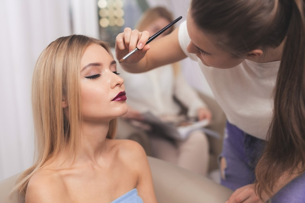 A blond girl is given make-up in a beauty salon